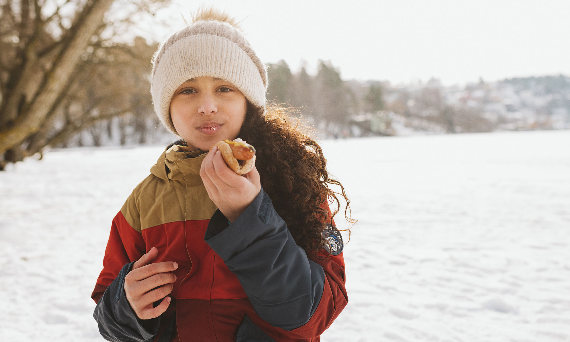 Wintertime - girl eating a hotdog outdoors